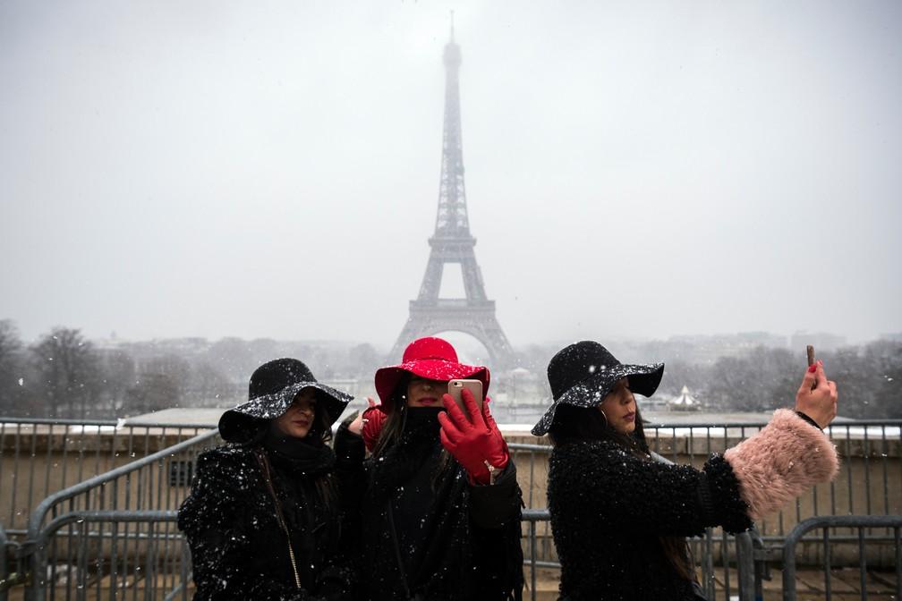 Turistas tiram foto sob neve nesta terça-feira (6) em Paris (Foto: Lionel Bonaventure/AFP)