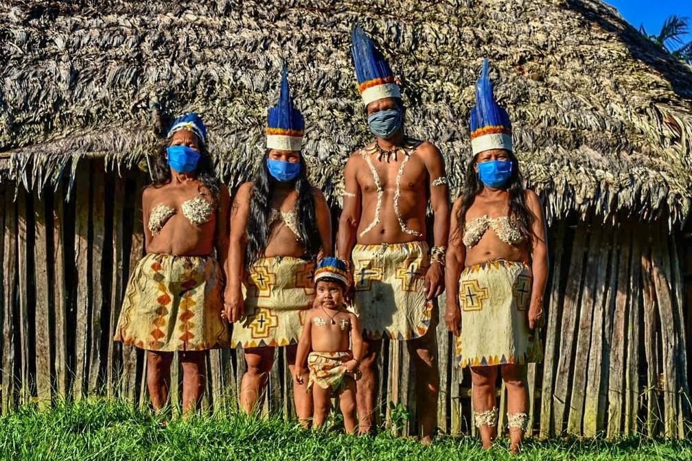 Povos indígenas Huitoto usam máscaras, na cidade de Leticia, na região da Amazônia colombiana, em meio a preocupação com a disseminação do novo coronavírus, na quarta-feira (20)  — Foto: Tatiana de Nevó / AFP