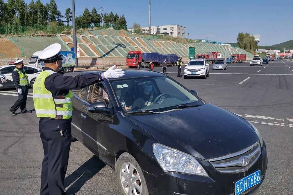 Policial orienta motorista em Jilin, na China, nesta quarta-feira (13). A cidade voltou a registrar casos de novo coronavírus — Foto: STR/AFP