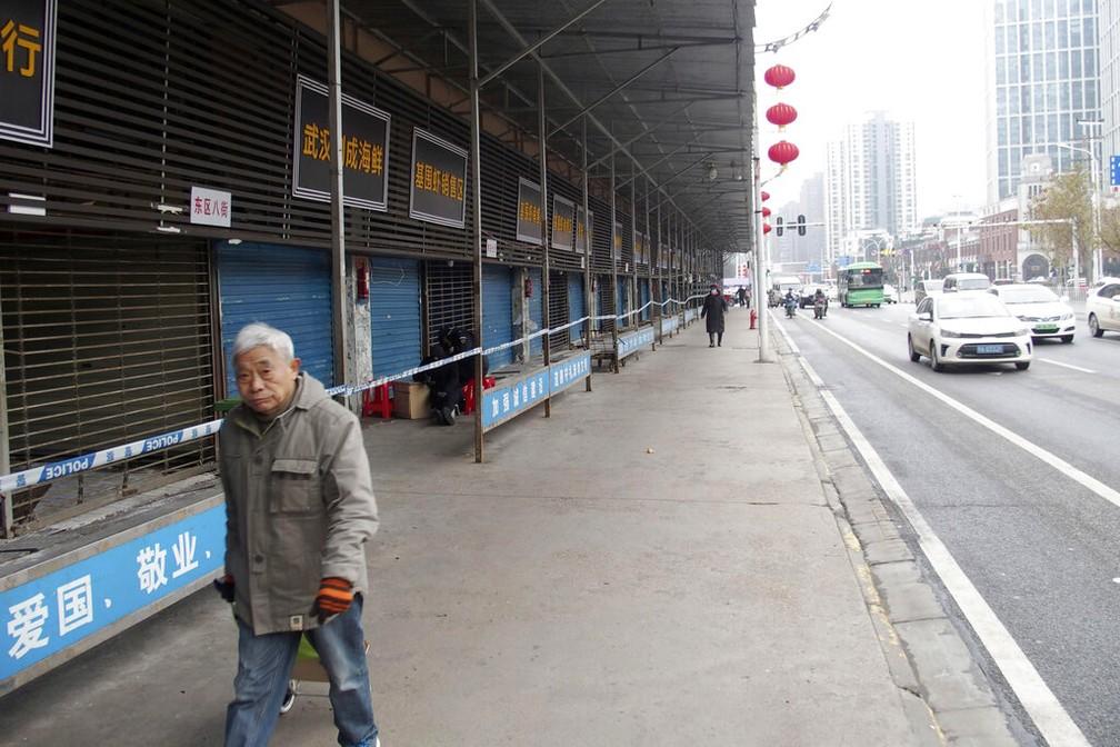 Homem passa por mercado de frutos do mar de Wuhan, foto de 23 de janeiro de 2020 — Foto: Kyodo News/AP/Arquivo