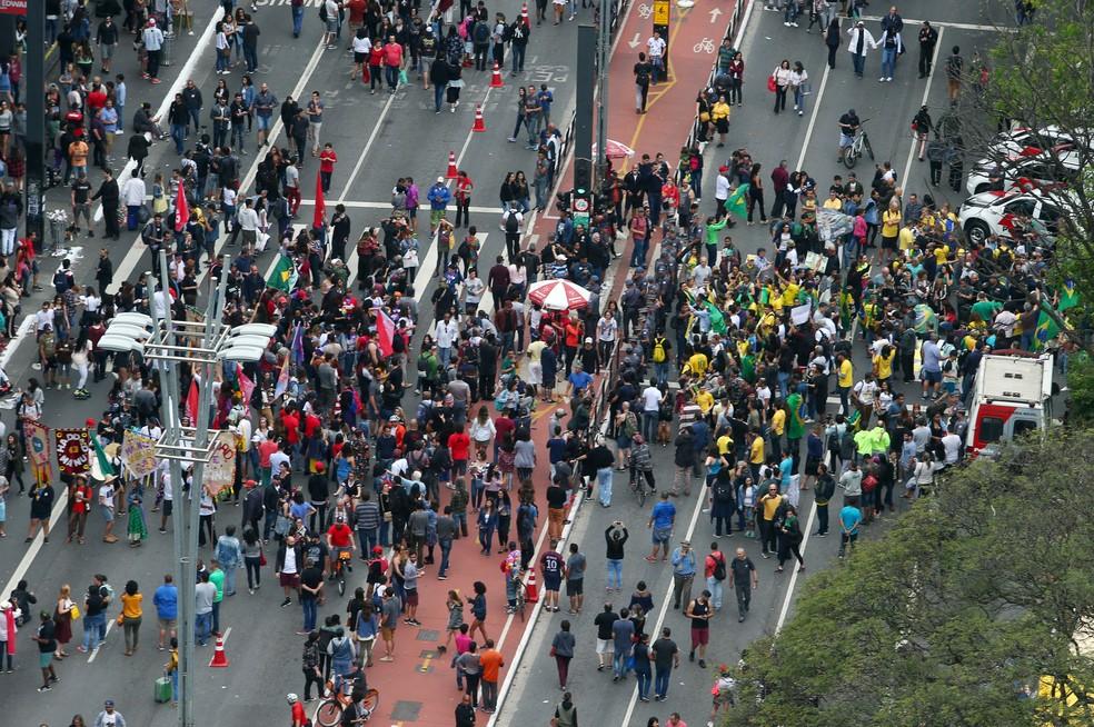 Apoiadores de Haddad, à esquerda, e de Bolsonaro, à direita, durante protestos neste domingo (14), na Avenida Paulista, em São Paulo — Foto: Reuters / Amanda Perobelli