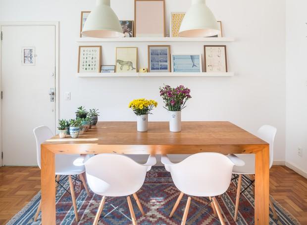 A mesa de madeira maciça faz fronteira com a cozinha do andar térreo, agora aberta para a área social do apartamento (Foto: Joana França/Divulgação)