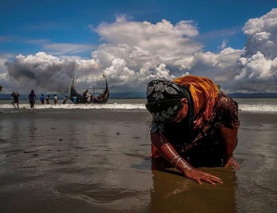 Exausta, refugiada rohingya toca a praia depois de cruzar de barco a fronteira entre Bangladesh e Mianmar (Foto: FOTÓGRAFOS/REUTERS)