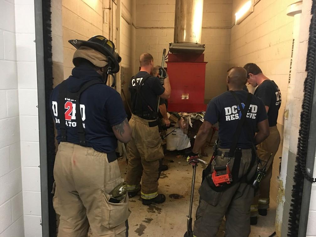 Bombeiros resgatam homem que caiu no lixo ao procurar celular perdido nos EUA (Foto: Vito Maggiolo/DC Fire and EMS Department via AP)