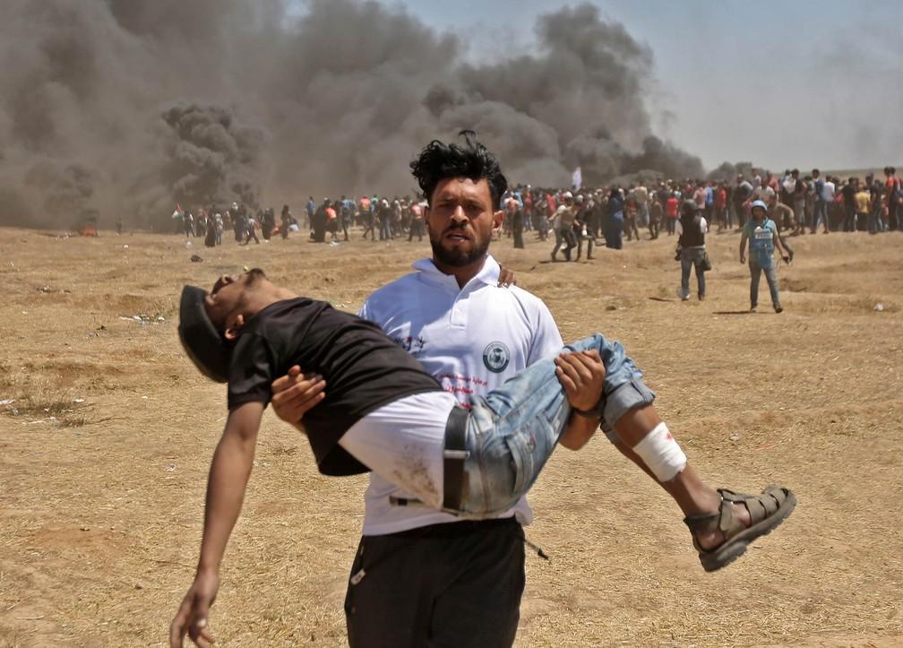 Palestino carrega no colo um companheiro manifestante ferido durante confronto com tropas israelenses perto da fronteira entre a Faixa de Gaza e Israel, no dia da abertura da Embaixada dos EUA em Jerusalém (Foto: Mahmud Hams/AFP)