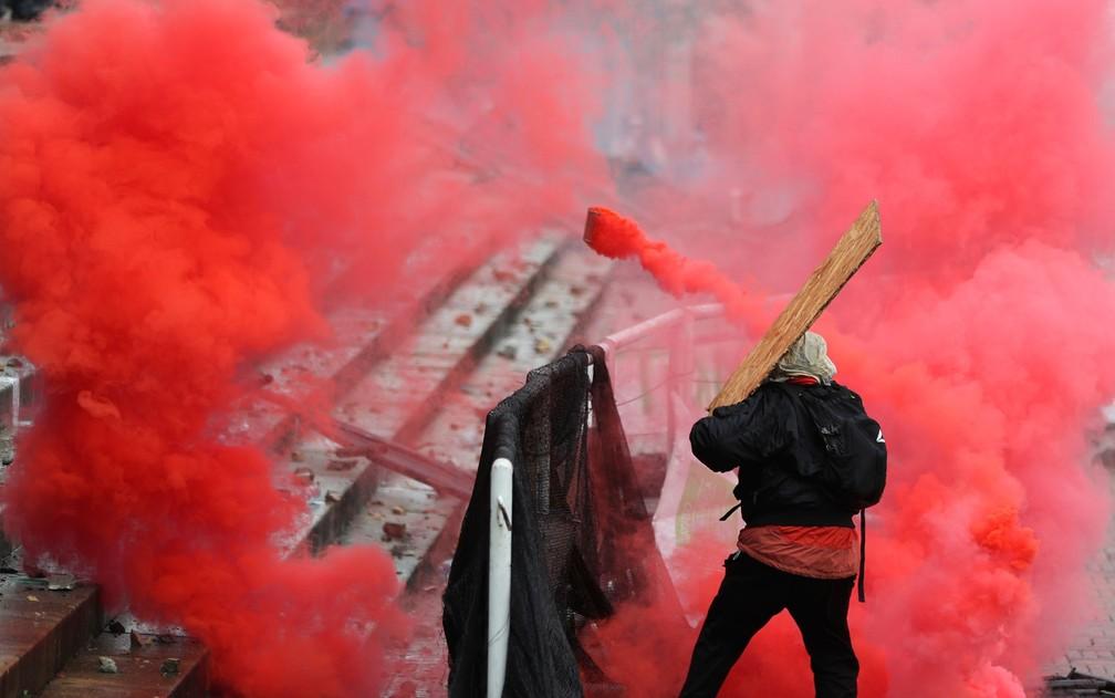 Manifestante usa pedaço de madeira para rebater lata de gás lacrimogêneo atirada pela polícia durante confronto em Bogotá, na Colômbia, na quarta-feira (5) — Foto: AP Photo/Fernando Vergara