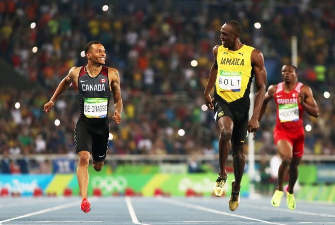Usain Bolt e Andre de Grasse brincam na linha de chegada (Foto: Getty Images)