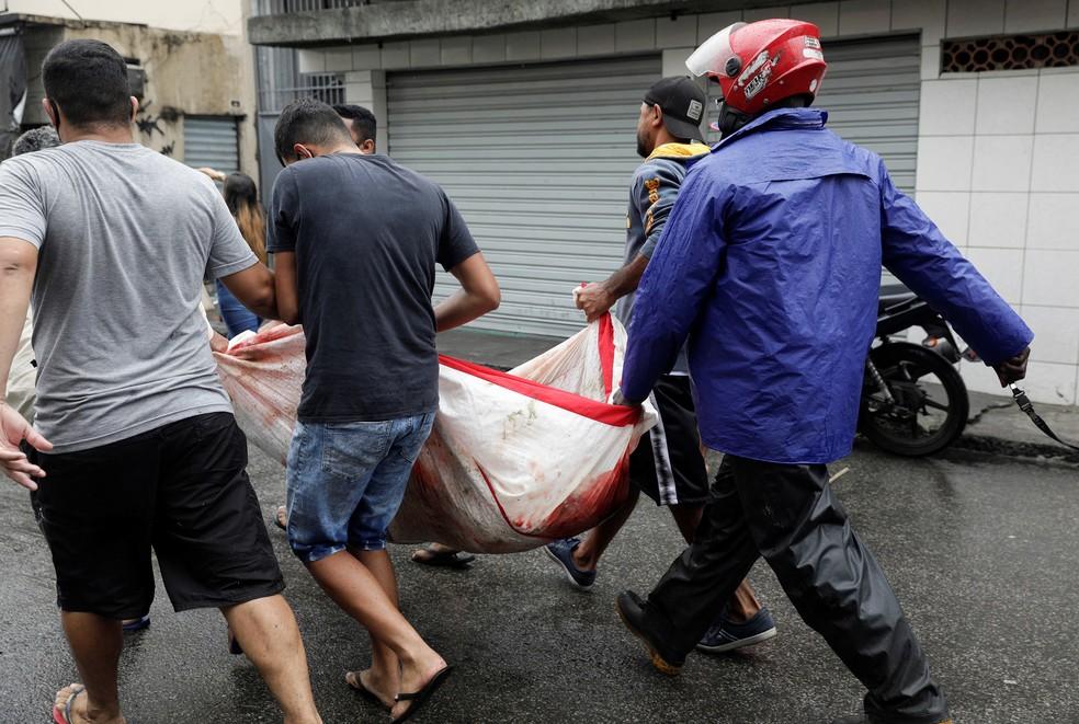 Moradores do Complexo do Alemão transportam corpo após operação policial, no Rio de Janeiro — Foto: Ricardo Moraes/Reuters