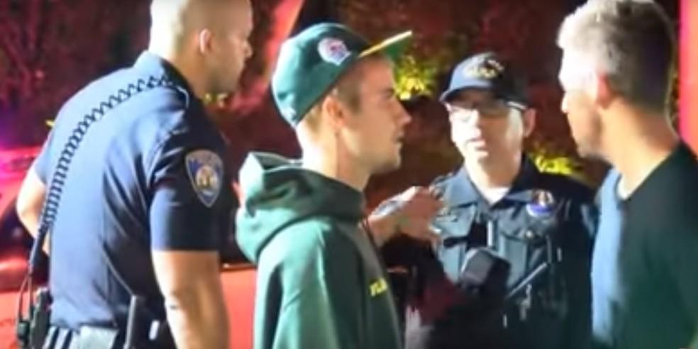 Justin Bieber conversa com policiais após atropelar fotógrafo (Foto: Reprodução)