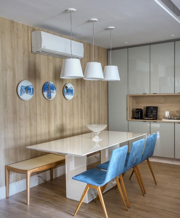 Combinação chique e casual, azul e carvalho aparecem juntos também na sala de refeições junto à cozinha (Foto: MCA Estúdio/Divulgação/Produção: Núria Uliana)