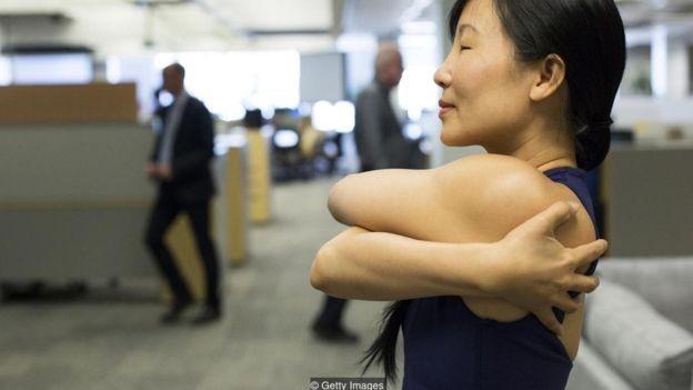 Um instrutora ensina técnicas de ioga a funcionários de uma empresa em Toronto, no Canadá (Foto: Getty Images via BBC)