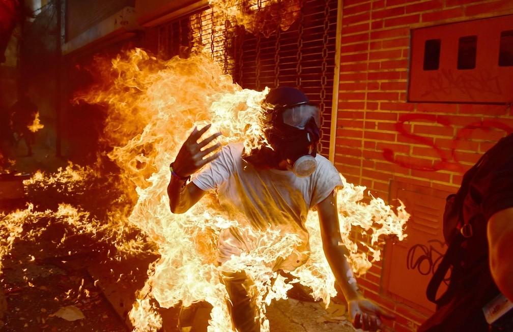 Corpo de manifestante pega fogo após explosão de tanque de gás durante protesto em Caracas, Venezuela — Foto: Ronaldo Schemidt/AFP