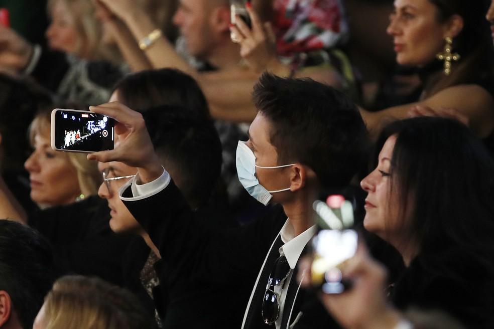 Homem usa máscara para assistir ao desfile da Dolce & Gabbana na Semana de Moda de Milão, na Itália — Foto: AP Photo/Antonio Calanni