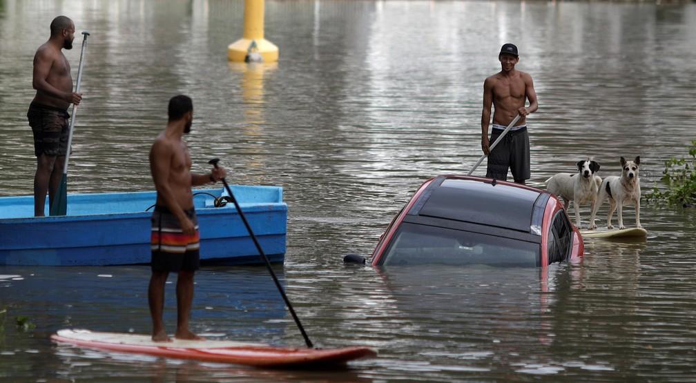 Moradores usam pranchas de SUP para se aproximar de um carro arrastado para canal na Barra da Tijuca após temporal que causou o alagamento de vias próximas — Foto: Ricardo Moraes/Reuters