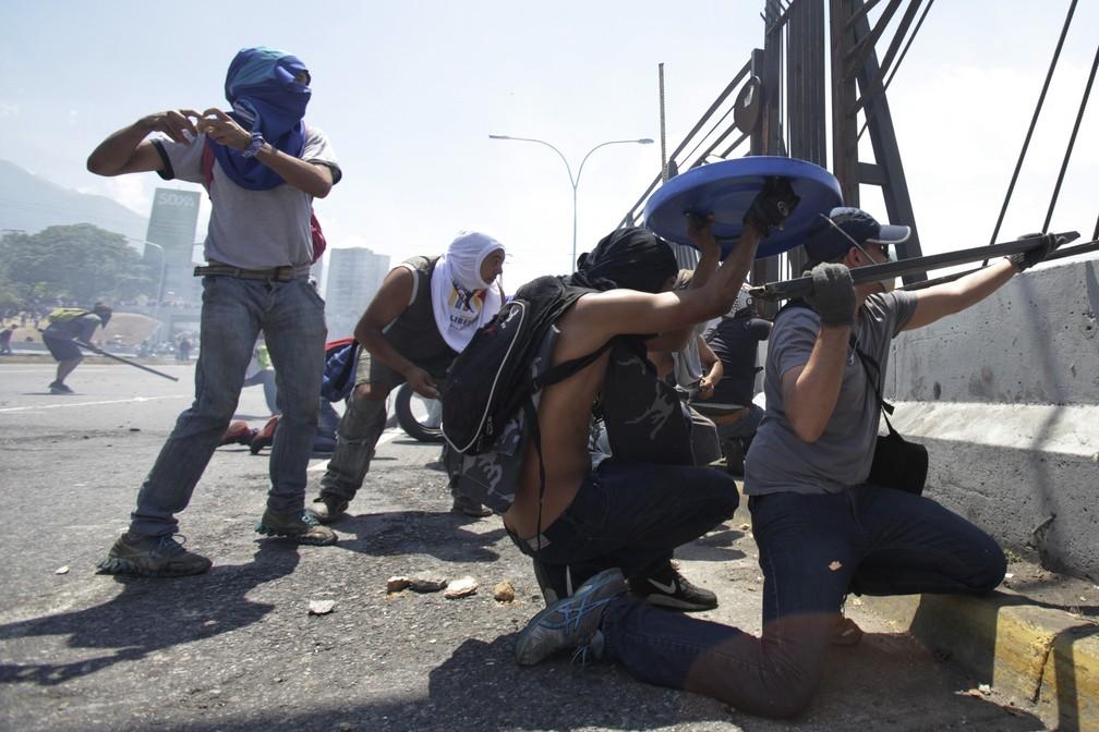 Adversários do presidente da Venezuela, Nicolas Maduro, desafiam as forças leais a Maduro na base aérea de La Carlota, em Caracas, na Venezuela — Foto: Boris Vergara/AP