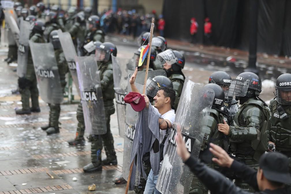 Homem tenta impedir que manifestantes joguem pedras contra a polícia durante uma greve nacional em Bogotá, na Colômbia, na quinta-feira (21). — Foto: Fernando Vergara/AP