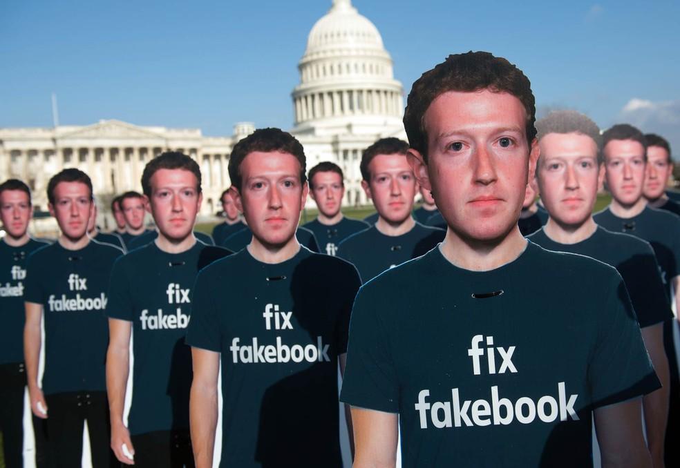 Recortes de papelão em tamanho real com o rosto do presidente do Facebook, Mark Zuckerberg, foram colocados diante do Capitólio, em Washington (EUA), com a frase 'Conserte o Fakebook', em protesto chamando atenção para milhões de contas falsas que seguem ativas e são usadas para espalhar 'fake news' — Foto: Saul Loeb/AFP
