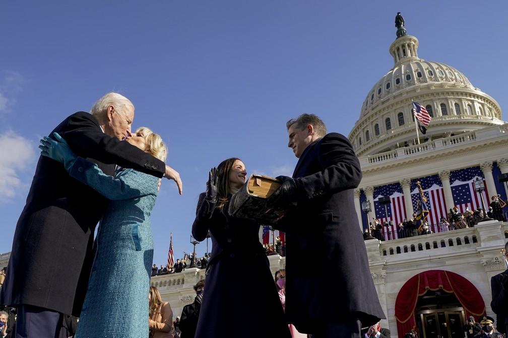 O presidente Joe Biden e a primeira-dama Jill Biden se beijam enquanto seu filho Hunter Biden e sua filha Ashley Biden se olham após Biden ser empossado durante a 59ª posse presidencial no Capitólio dos Estados Unidos, em Washington, nesta quarta-feira (20)  — Foto: Andrew Harnik/Pool via AP