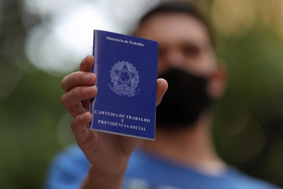 Homem segurando carteira de trabalho. — Foto: Amanda Perobelli/Reuters