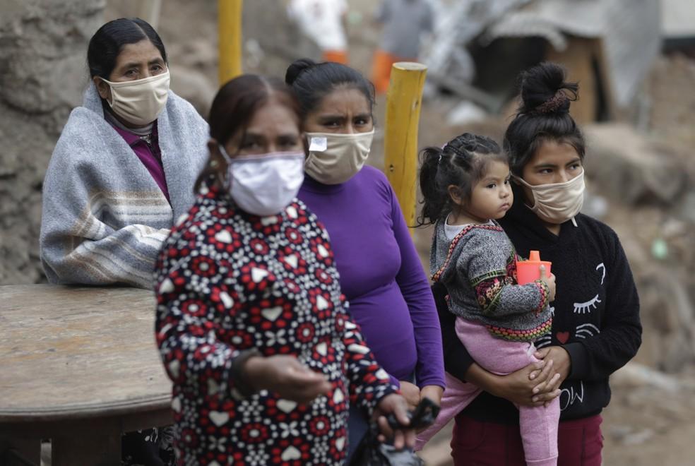 27 de maio: mulheres usando máscaras contra a Covid-19 esperam refeição na favela de Flor de Amancaes, perto de Lima, no Peru. — Foto: Martin Mejia/AP