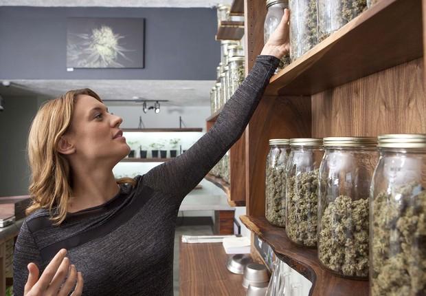 Mulher escolhe pote com maconha dentro de loja (Foto: Heath Korvola via Getty Images)