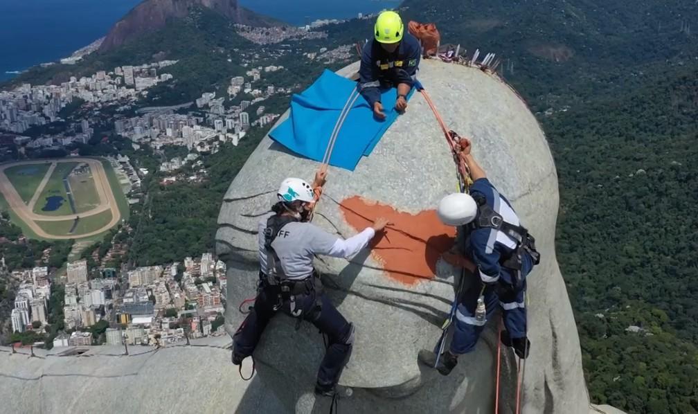 Cristina Ventura e equipe de trabalho na cabeça do Cristo Redentor durante restauro — Foto: Imagens do Drone Igor Souza
