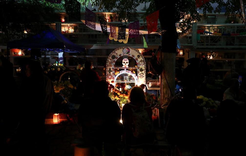 Pessoas fazem homenagens ao redor do túmulo de entes queridos no cemitério Los Reyes, na Cidade do México, durante as celebrações do Dia dos Mortos nesta sexta (1º) — Foto: Eduardo Verdugo/AP