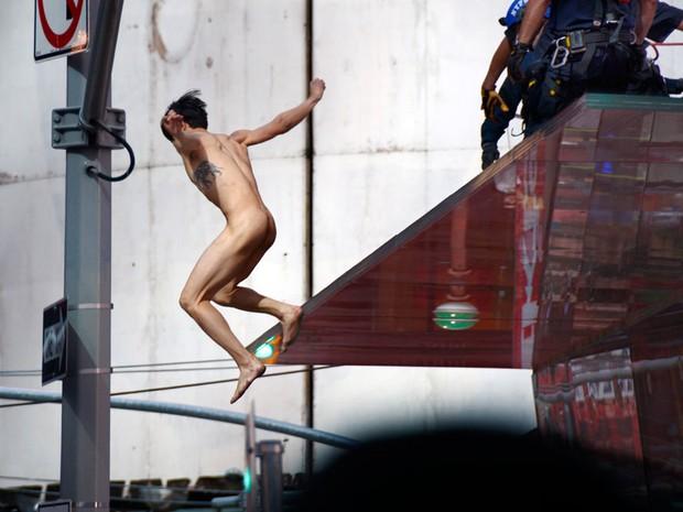 Homem nu pula de arquibancada na Times Square, em Nova York (Foto: AP)