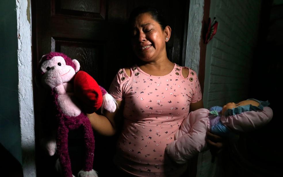 Rosa Ramírez, mãe de Óscar e avó de Angie, chora enquanto mostra os brinquedos da neta morta no Rio Grande — Foto: Antonio Valladares/AP