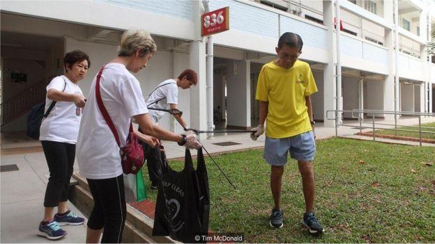 Voluntários no dia de limpeza de Khatib, embora já existam 56.000 faxineiros registrados em Cingapura (Foto: TIM MCDONALD via BBC News Brasil)