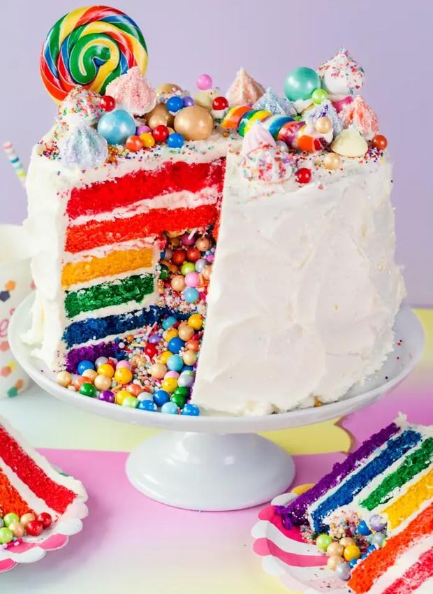 Bolo surpresa de arco-íris: cada camada de massa leva uma cor, enquanto o centro guarda docinhos coloridos (Foto: Pinterest/ Reprodução)