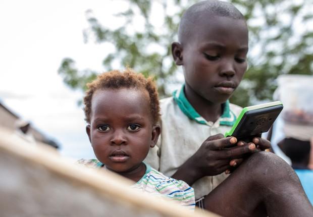 Crianças usam celular em Nsonga, em Uganda (Foto:  Jack Taylor/Getty Images)