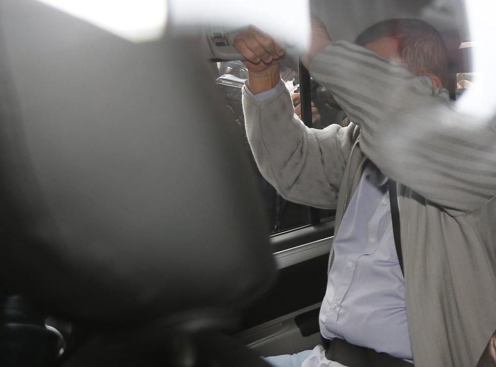 Geddel Vieira Lima cobre o rosto ao chegar para depoimento à Justiça Federal em Brasília (Foto: Dida Sampaio/Estadão Conteúdo)