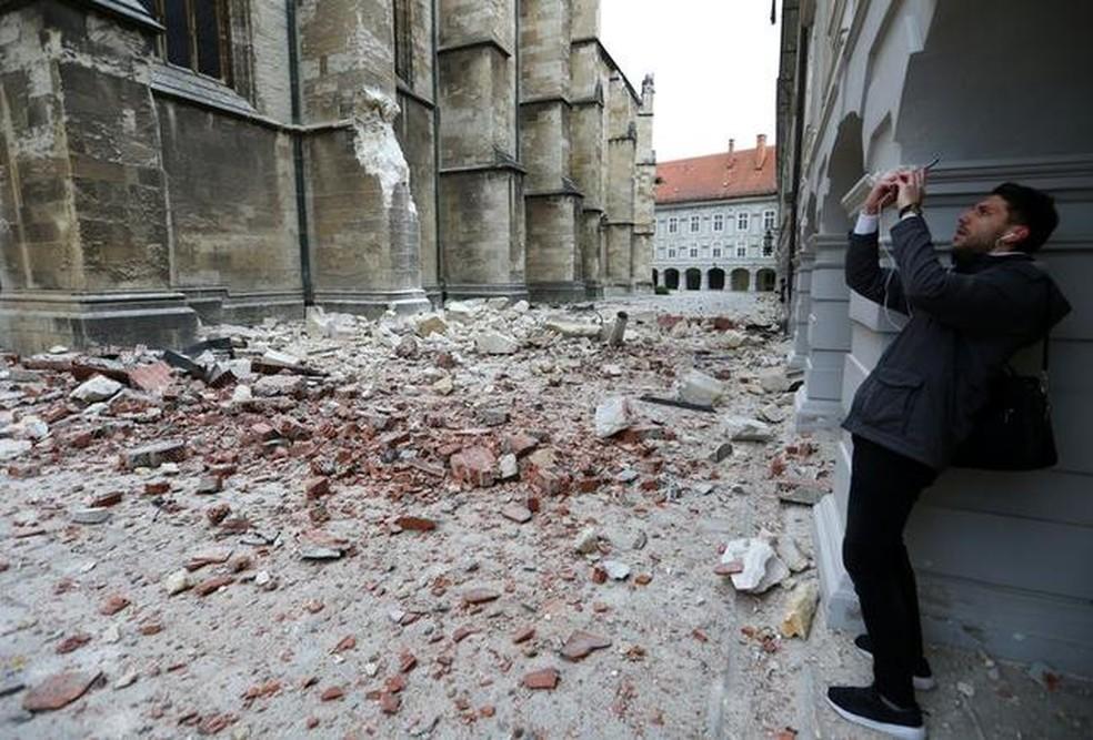 Homem observa e fotografa os estragos do lado de fora da Catedral de Zagreb — Foto: Antonio Bronic/Reuters