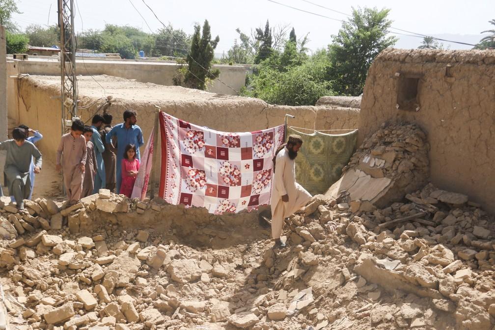 Moradores se reúnem perto de casa danificada por terremoto na cidade de Harnai, na província de Baluchistão, em 7 de outubro de 2021 no Paquistão — Foto: Naseer Ahmed/Reuters
