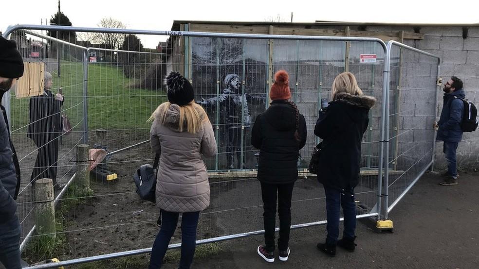 A pintura foi cercada com grades para evitar roubo e vandalismo — Foto: BBC