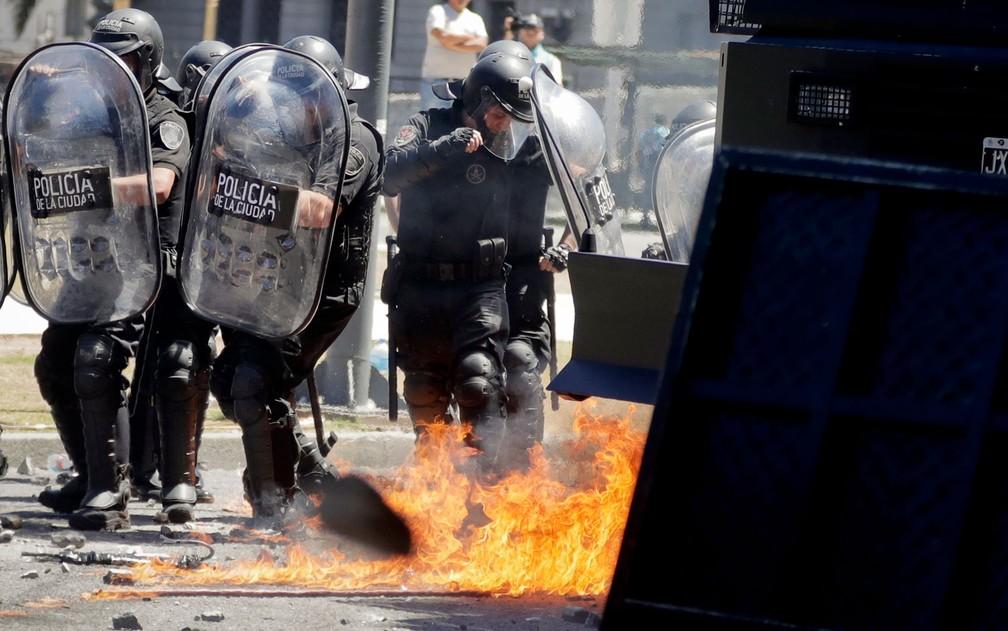 Policiais passam por destroços incendiados por manifestantes durante protesto contra a reforma da previdência em Buenos Aires, na Argentina, na segunda-feira (18) (Foto: AP Photo/Victor R. Caivano)